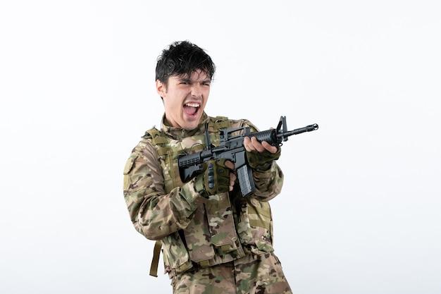 Vista frontal del joven soldado luchando con ametralladora pared blanca