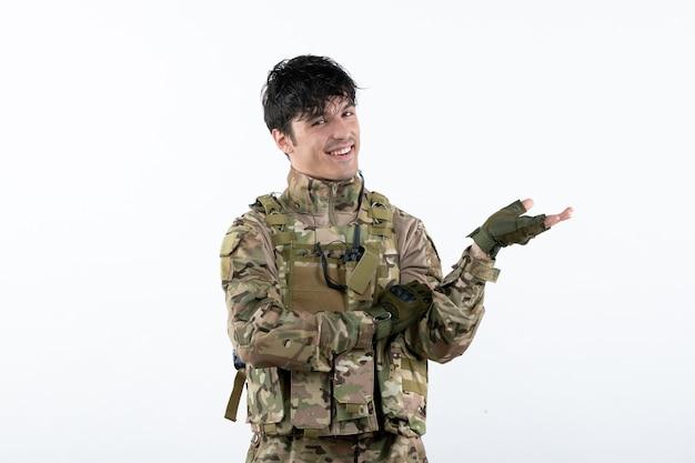 Vista frontal del joven soldado sonriente en uniforme militar en la pared blanca