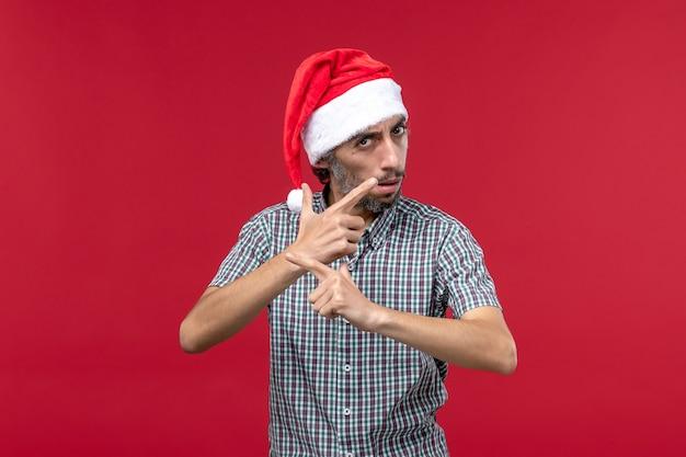 Vista frontal joven solo de pie en la pared roja vacaciones rojo año nuevo macho