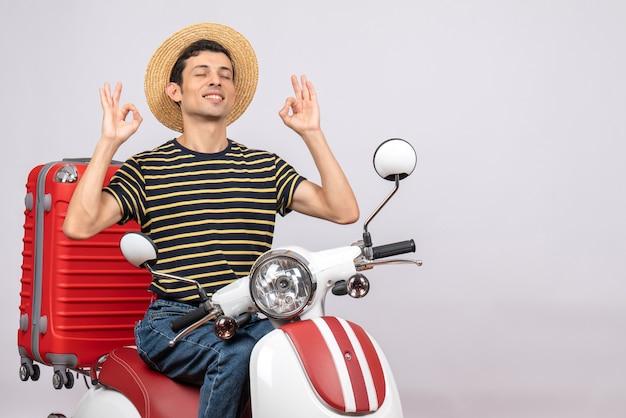 Vista frontal del joven con sombrero de paja en ciclomotor cerrando los ojos haciendo el signo de ok