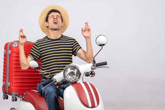Vista frontal del joven con sombrero de paja en ciclomotor haciendo deseo firmar con los ojos cerrados