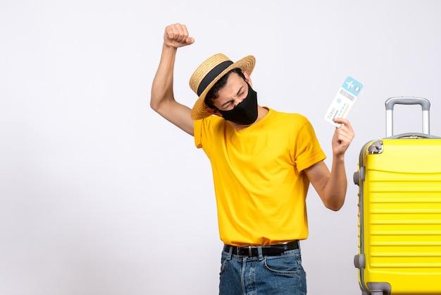 Vista frontal joven con sombrero de paja de pie cerca de la maleta amarilla con boleto de viaje expresando sus sentimientos