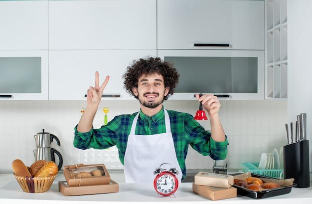 Vista frontal del joven sonriente de pie detrás de la mesa con varios pasteles y mostrando la campana del anillo rojo haciendo el gesto de la victoria en la cocina blanca