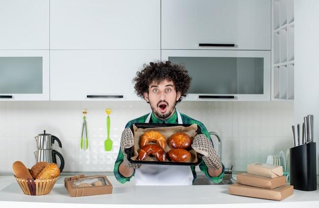 Vista frontal del joven sorprendido con soporte mostrando pasteles recién horneados en la cocina blanca