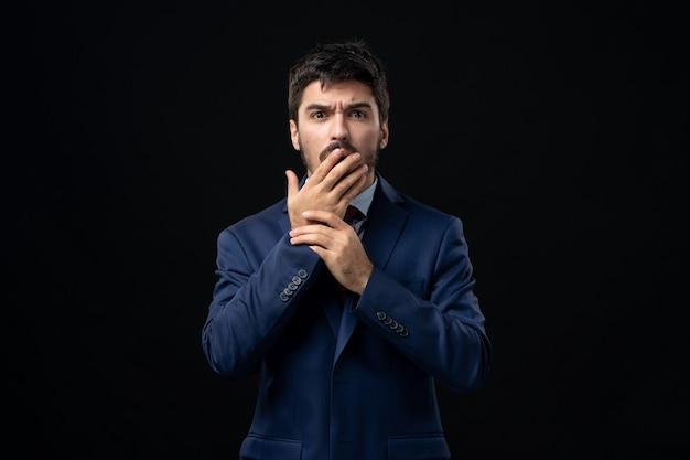 Vista frontal del joven sorprendido en traje en pared oscura aislada