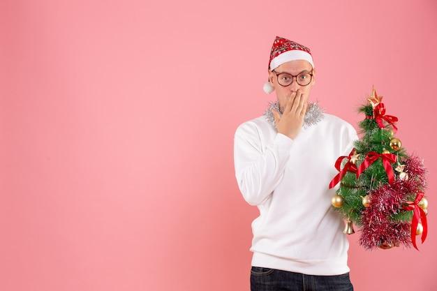 Vista frontal del joven sosteniendo arbolito de navidad en pared rosa