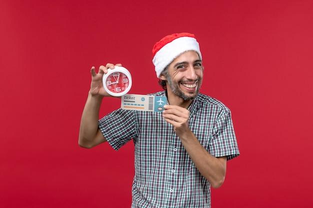 Vista frontal joven sosteniendo el billete y el reloj en la pared de color rojo claro tiempo de emoción masculina roja