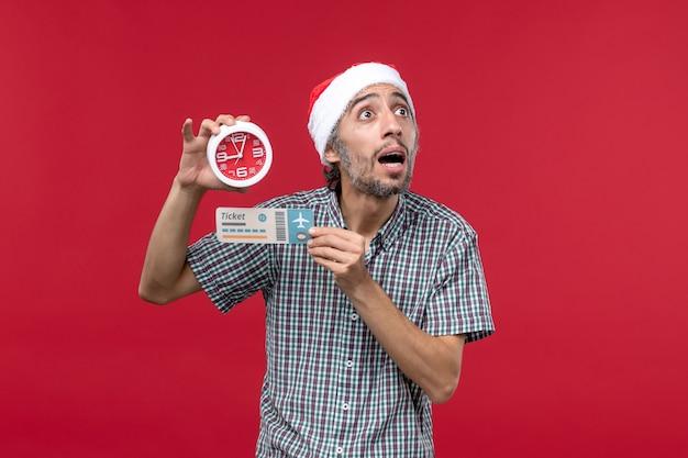 Vista frontal joven sosteniendo billete y reloj en pared roja vuelo rojo emoción tiempo
