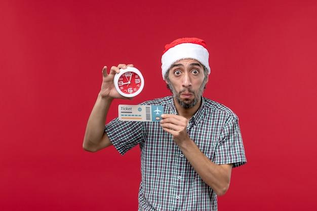 Vista frontal joven sosteniendo boleto y reloj en pared roja tiempo de emoción masculina roja