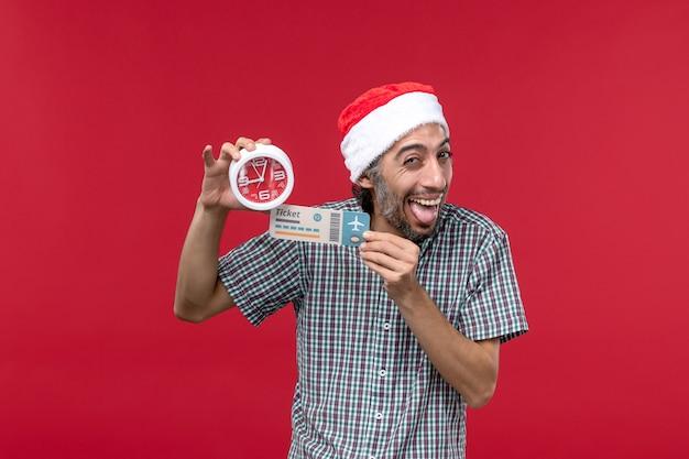 Vista frontal joven sosteniendo boleto y reloj en pared roja tiempo de emociones masculinas rojas