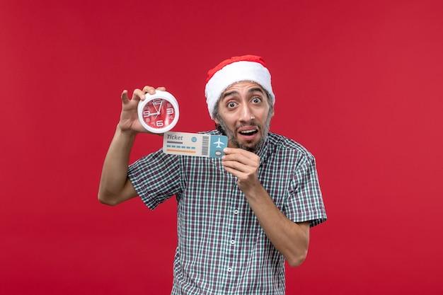 Vista frontal joven sosteniendo boleto y reloj en piso rojo tiempo de emoción masculina roja