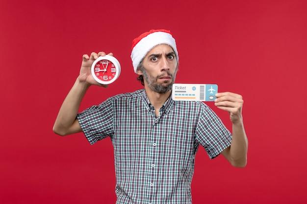 Vista frontal joven sosteniendo el boleto con reloj sobre fondo rojo.