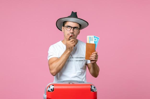 Vista frontal del joven sosteniendo boletos de avión preparándose para las vacaciones en la pared rosa