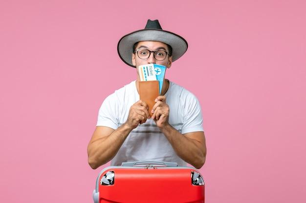 Vista frontal del joven sosteniendo boletos de vacaciones en la pared rosa