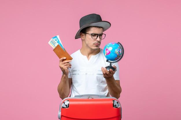 Vista frontal del joven sosteniendo boletos de vacaciones y pequeño globo en la pared rosa