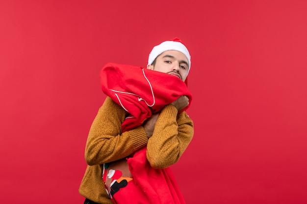Vista frontal del joven sosteniendo la bolsa actual en la pared roja