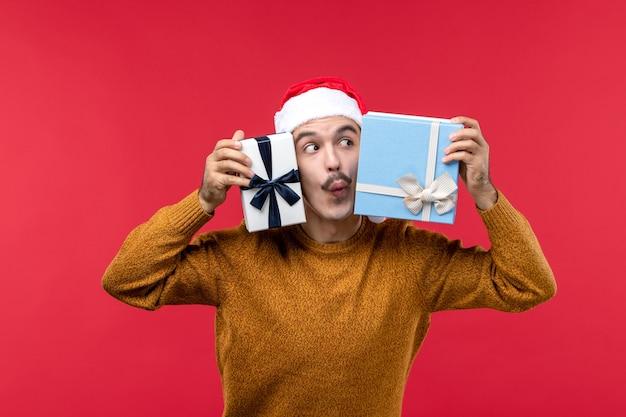Vista frontal del joven sosteniendo cajas presentes en la pared roja