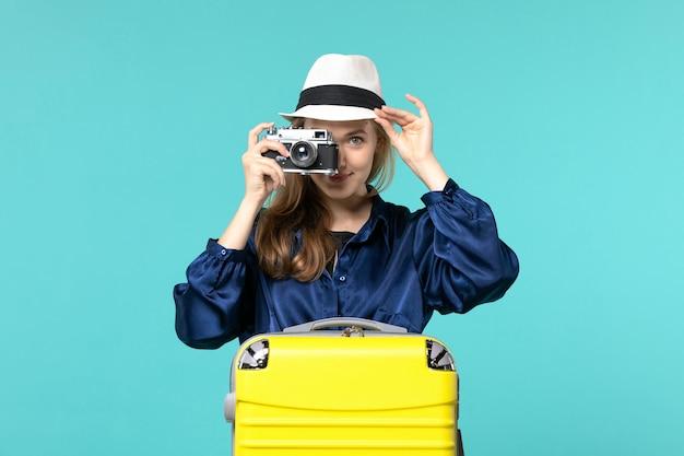 Vista frontal joven sosteniendo la cámara y tomando fotos en el fondo azul mujer viaje mar viaje avión de viaje