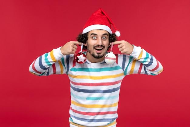 Vista frontal joven sosteniendo juguetes de árbol de navidad en la pared roja año nuevo rojo vacaciones macho