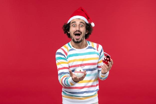 Vista frontal joven sosteniendo juguetes de árbol de navidad en la pared roja vacaciones año nuevo humano