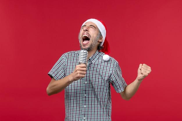 Vista frontal joven sosteniendo el micrófono y gritando en la pared roja música cantante de vacaciones masculina