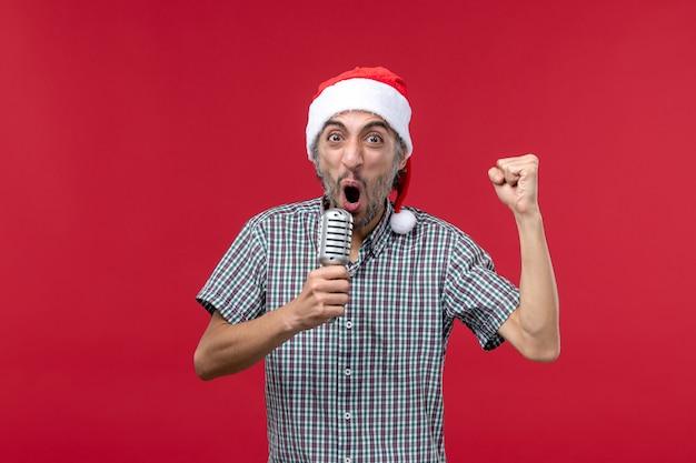 Vista frontal joven sosteniendo el micrófono en la pared roja música cantante de vacaciones de emoción masculina