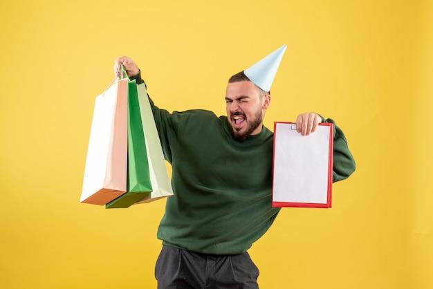 Vista frontal joven sosteniendo paquetes de compras y nota sobre fondo amarillo