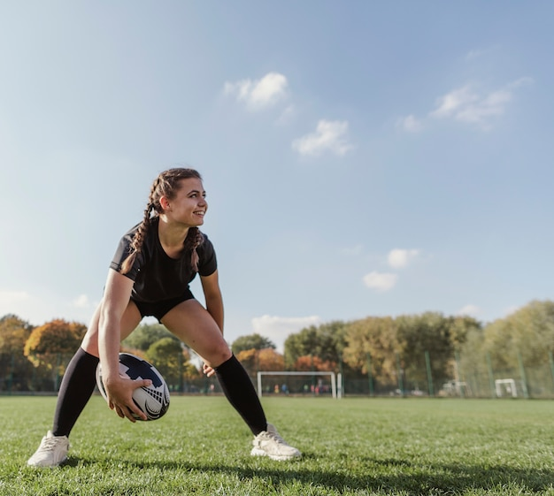 Vista frontal joven sosteniendo una pelota de rugby con espacio de copia