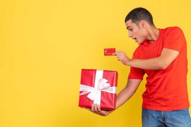 Vista frontal del joven sosteniendo presente y tarjeta bancaria en la pared amarilla