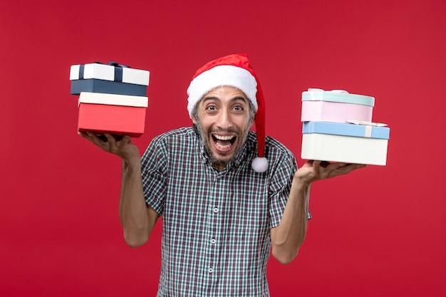 Vista frontal joven sosteniendo regalos sobre fondo rojo.