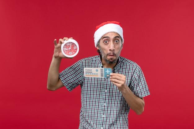 Vista frontal joven sosteniendo el reloj y el boleto en la pared roja roja emoción tiempo masculino