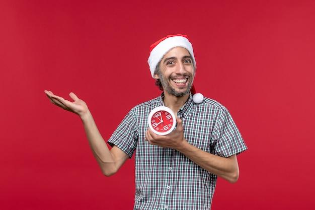 Vista frontal joven sosteniendo relojes con expresión sonriente en la pared roja tiempo de emoción roja