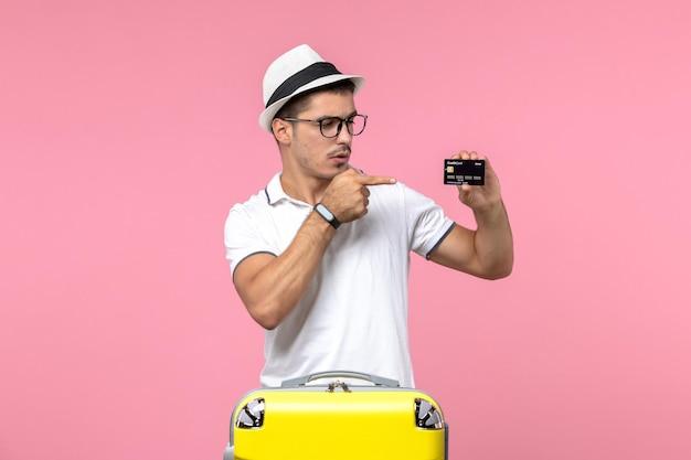 Vista frontal del joven sosteniendo una tarjeta bancaria negra en la pared rosa