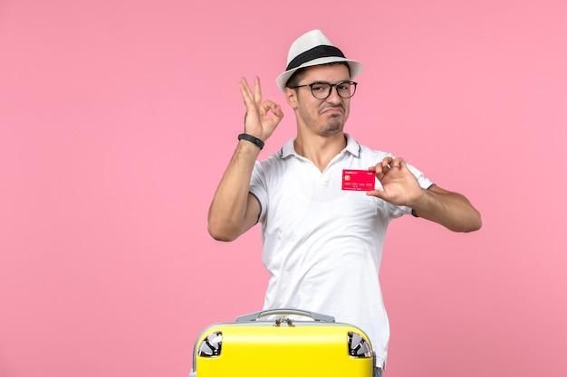 Vista frontal del joven sosteniendo una tarjeta bancaria roja en la pared rosa