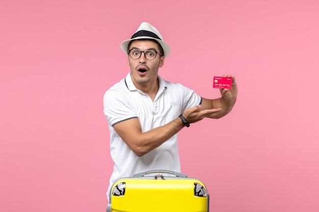 Vista frontal del joven sosteniendo una tarjeta bancaria roja en vacaciones de verano en la pared rosa