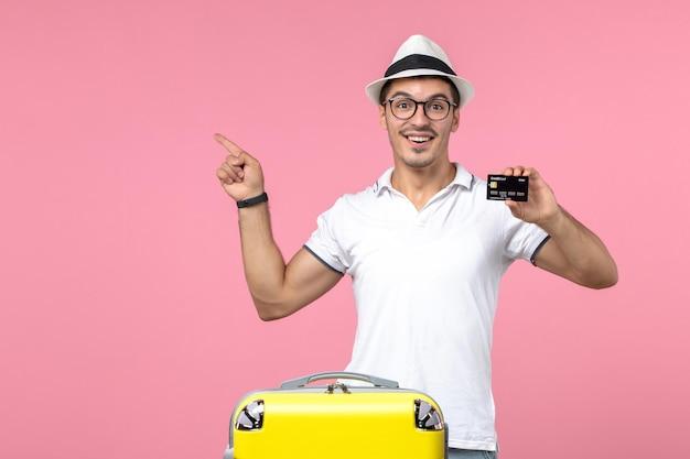 Vista frontal del joven sosteniendo una tarjeta bancaria de vacaciones en la pared rosa
