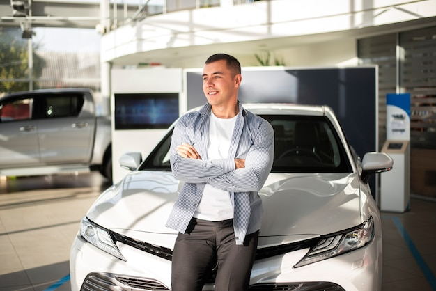 Vista frontal joven con su auto nuevo