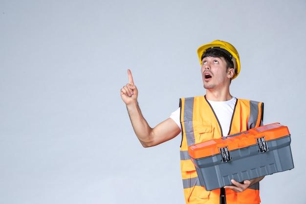 Vista frontal joven trabajador sosteniendo maletín de herramientas pesadas sobre fondo blanco.