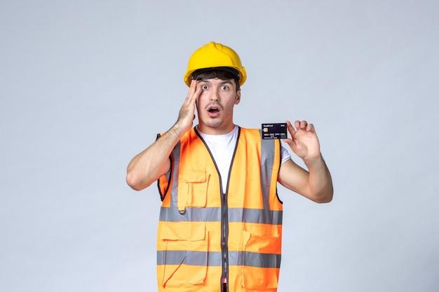 Vista frontal joven trabajador con tarjeta bancaria negra sobre fondo blanco.