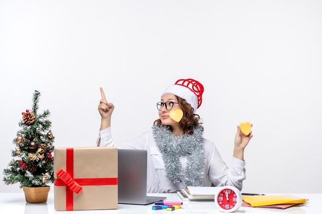 Vista frontal joven trabajadora sentada ante su lugar sosteniendo pegatinas en el escritorio blanco