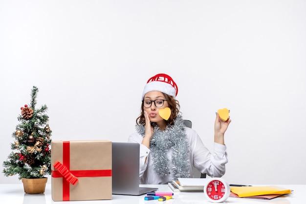 Vista frontal joven trabajadora sentada ante su lugar sosteniendo pegatinas sobre fondo blanco.