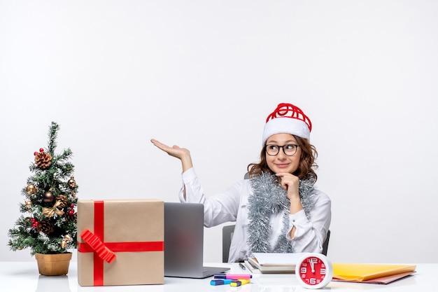 Vista frontal joven trabajadora sentada ante su lugar de trabajo pensando en fondo blanco
