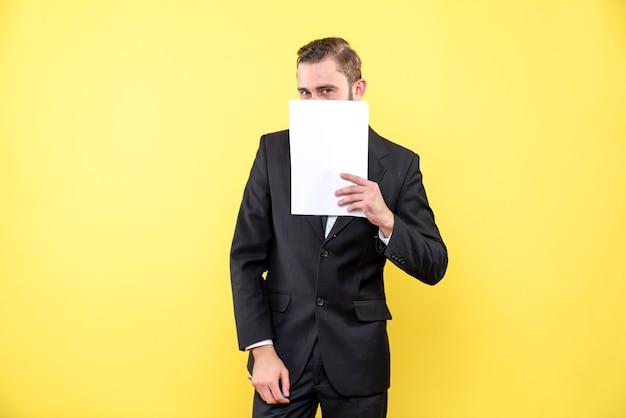 Vista frontal del joven en traje negro que oculta la parte inferior de la cara con papel en blanco en la pared amarilla