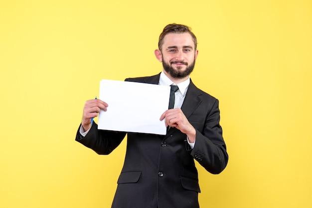 Vista frontal del joven en traje negro sonriendo alegremente y sosteniendo hojas de papel en blanco en amarillo