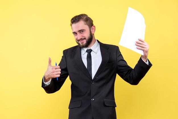 Vista frontal del joven en traje negro sosteniendo papel en blanco sobre amarillo con sonrisa pulgar hacia arriba con los dedos excelente signo