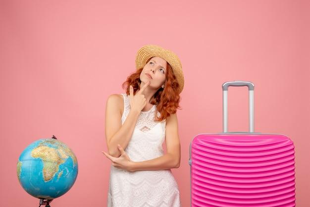 Vista frontal de la joven turista con bolsa rosa pensando en pared rosa