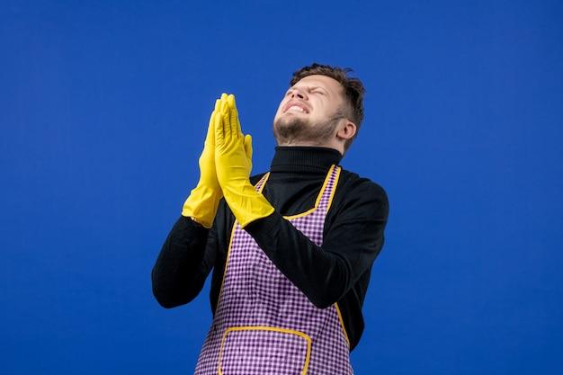 Vista frontal del joven uniendo sus manos juntas y deseando en la pared azul