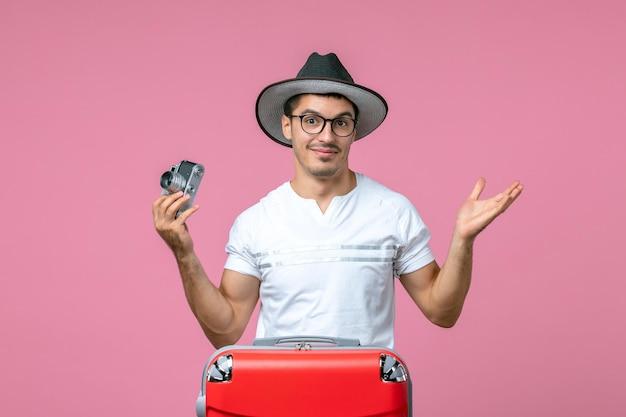 Vista frontal del joven de vacaciones con bolsa roja sosteniendo la cámara en la pared rosa