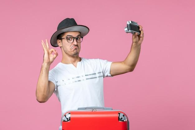 Vista frontal del joven en vacaciones con bolsa sosteniendo la cámara tomando fotos en la pared rosa claro