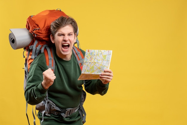 Vista frontal joven varón preparándose para senderismo sosteniendo mapa con expresión enojada